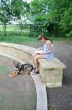 Flickaläsning parkerar in med hunden Fotografering för Bildbyråer