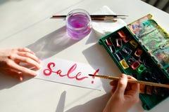 Flickamålaren skriver med borsten och målar inskriften på arket, Royaltyfria Foton