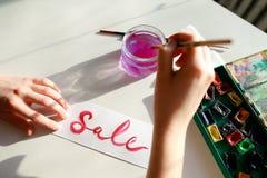 Flickamålaren skriver med borsten och målar inskriften på arket, Arkivbilder