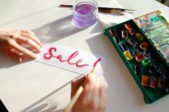 Flickamålaren skriver med borsten och målar inskriften på arket, Arkivfoto