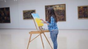 Flickamålning på kanfas i konstgalleri stock video