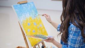 Flickamålningblått blommar på en kanfas arkivfilmer