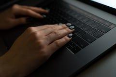 Flickamaskinskrivning på metallbärbara datorn med lågt ljus royaltyfri foto