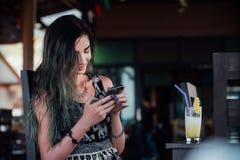 Flickamaskinskrivningen i telefonen, sammanträde i ett kafé med fruktananasfruktsaft i ett exponeringsglas och ett rör Arkivbilder