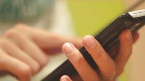 Flickamaskinskrivningtext på din telefon, inomhus, närbild, fingeravtryck på skärmen av telefonen, visartavlor ett nummer arkivfilmer