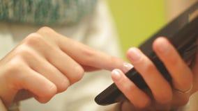 Flickamaskinskrivningtext på din telefon, inomhus, närbild, fingeravtryck på skärmen av telefonen, visartavlor ett nummer stock video
