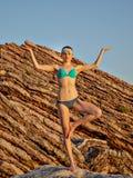 Flickameditationen vaggar på bakgrund under solnedgång Yogan poserar Kondition och en sund livsstil royaltyfri bild