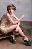 Flickamodell som bär lyxiga guld- klänning- och plattformsandaler Royaltyfri Fotografi