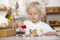 flickamontessori som pre leker skolabarn royaltyfri bild