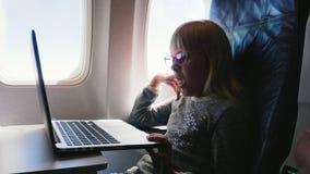Flickan är 6 år gammalt flyg i ett flygplan Lite uttråkat, önskar att sova och gäspar Ser tecknade filmer på bärbara datorn arkivfilmer