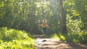 Flickan är banhoppningrepet i parkera Ung flicka som gör sportar i skogen arkivfilmer