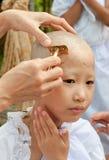 Flickan är borttaget hår som blir en nunna under en buddistisk ordinatio Royaltyfria Bilder