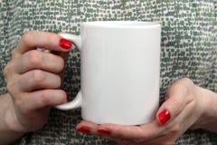Flickan är den hållande vita koppen i händer Arkivbilder