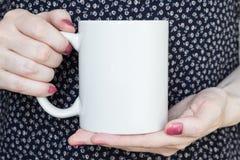 Flickan är den hållande vita koppen i händer Royaltyfria Foton