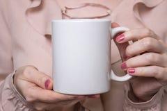 Flickan är den hållande vita koppen i händer Vit rånar för kvinnan, gåva Modell för designer Royaltyfria Bilder
