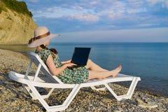 Flickan är en freelancer som tycker om det härliga öppna havet sitta pÃ¥ en soldagdrivare bredvid din bärbar dator Sikten frå arkivfoton