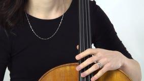 Flickan är en musiker sitter och spela violoncellen close upp arkivfilmer