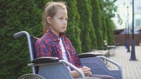 Flickan är en rörelsehindrad person i en rullstol Fotografering för Bildbyråer