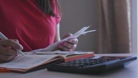 Flickan är en revisor, skriver nummer till en anteckningsbok, ser kontroller, sätter dem på en räknemaskin Rörelse av arkivfilmer