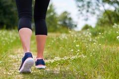 Flickan är förlovad i cardio körningar till och med skog i gymnastikskor, endast ben är synlig, ben och gymnastikskor Royaltyfri Bild
