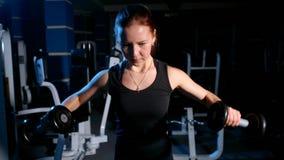 Flickan är förlovad i idrottshallen Övning på de deltaformade musklerna med en hantel arkivfilmer