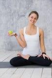 Flickan är förlovad i yoga på en vit bakgrund, begrepp av den sunda livsstilen, sunt äta och sporten, äpplen Royaltyfri Fotografi
