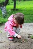 Flickan är försiktig undersöka snigeln arkivbilder