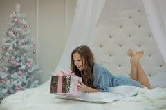 Flickan är förvånad och lycklig med julklapp i hennes handlögner i morgonen i hennes vitrundasäng i sovrummet med ett n royaltyfri foto