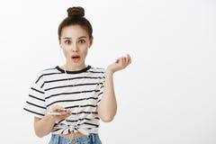 Flickan är fantastisk nyheterna för chockad utfrågning som avbryts av lyssnande musik i earbuds Häpen snygg kvinnlig kvinna med royaltyfria bilder