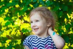 Flickan är framsidan på en bakgrund av gröna druvatjänstledigheter arkivbild