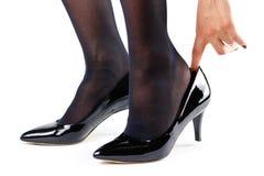 Flickan är iklädda svarta skor close upp Isolerat på en whit Arkivbild