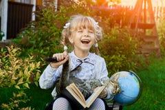 Flickan är lycklig med slutet av skolåret royaltyfria foton