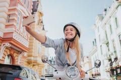 Flickan är sitta och luta till kontroll för motorcykel` som s headling och tar selfie Hon rymmer telefonen i hand Flickan är arkivfoton