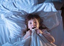 Flickan är skrämt ligga i säng Royaltyfri Fotografi