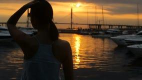 Flickan är tillbaka i solglasögon på solnedgången i sommar lager videofilmer