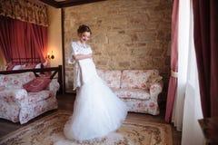 Flickan är yr i hennes hemtrevliga rum som försöker på en bröllopsklänning Bruden beundrar hennes dress för bröllopdagen royaltyfri bild