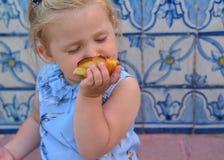 Flickan äter det syrliga Pasteis de Belem ägget, typisk portugisisk efterrätt Royaltyfria Foton