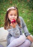 Flickan äter det utomhus- äpplet royaltyfri bild