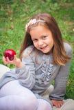 Flickan äter det utomhus- äpplet royaltyfri fotografi