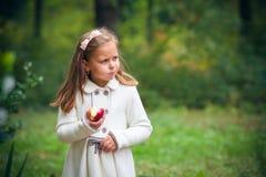 Flickan äter det utomhus- äpplet arkivfoton