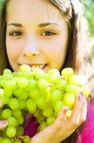 Flickan äter druvor Arkivfoto