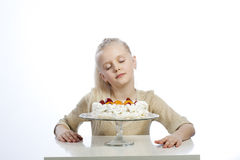 Flickan äter en kaka royaltyfria bilder
