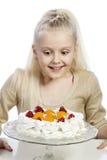 Flickan äter en kaka royaltyfria foton