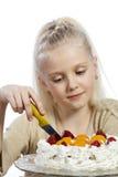 Flickan äter en kaka royaltyfri fotografi