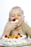 Flickan äter en kaka arkivbild
