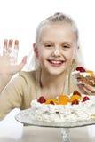 Flickan äter en kaka arkivfoto