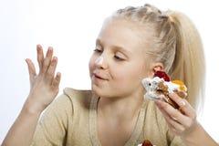 Flickan äter en kaka fotografering för bildbyråer