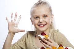 Flickan äter en kaka arkivfoton