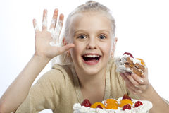 Flickan äter en kaka royaltyfri bild