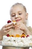 Flickan äter en kaka arkivbilder